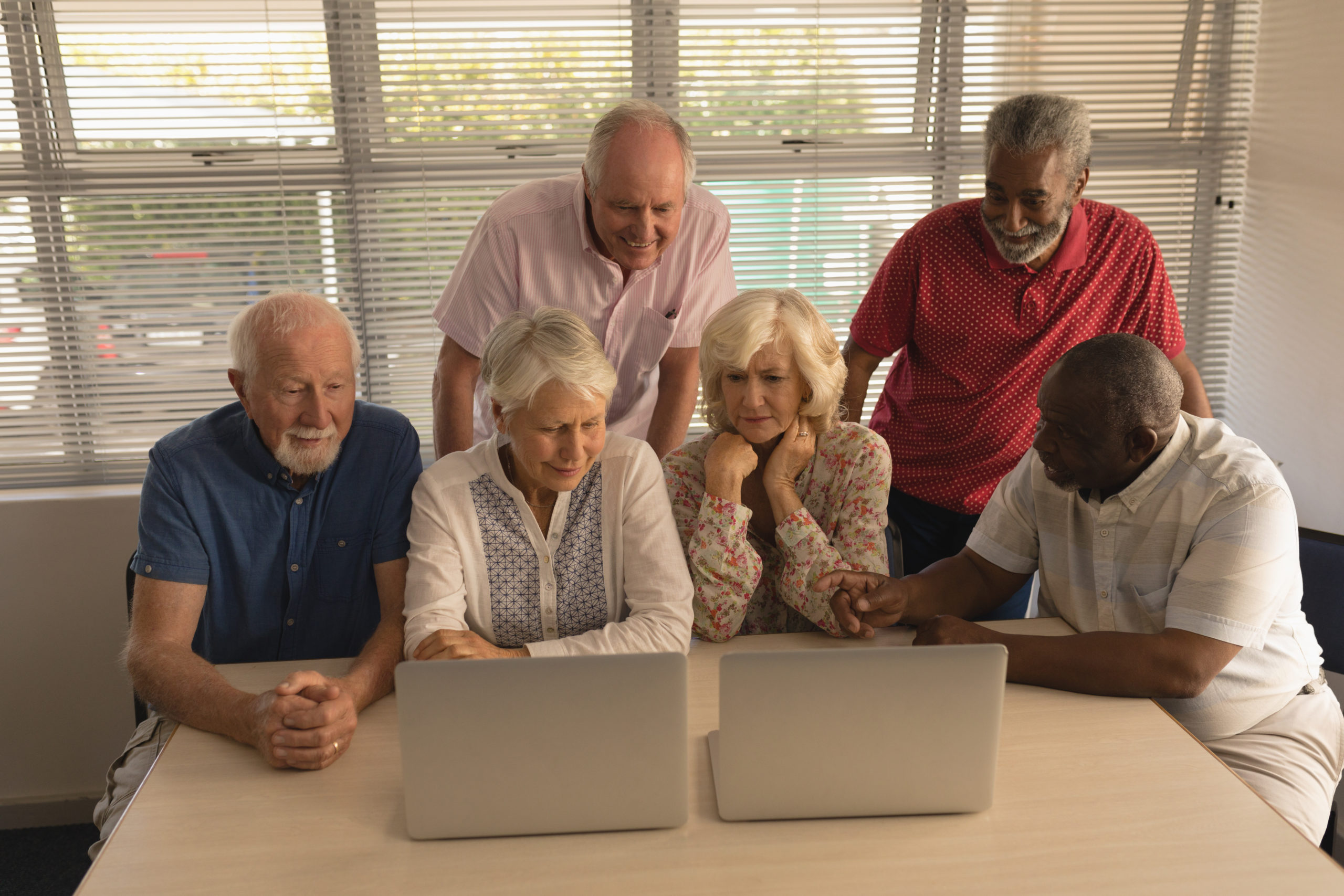 Front view of group of concentrated active senior people using laptop at nursing home.